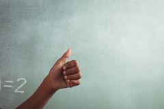Cropped hand of student showing thumb against blackboard Royalty Free Stock Photo