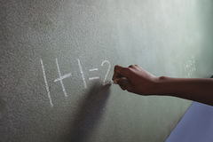 Cropped hand of student writing on blackboard. In classroom Stock Photo