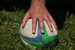 Cropped hand touching rugby ball. Cropped image of hand touching rugby ball on field stock images