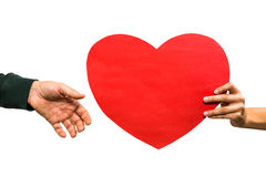 Cropped hand of woman giving heart shaped paper to man Stock Photo