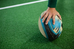 Cropped hand of woman holding rugby ball. On field stock photo