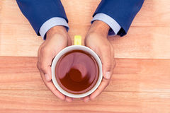 Cropped hands of businessman holding coffee cup Stock Image
