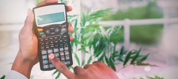 Composite image of cropped hands of businessman using calculator Royalty Free Stock Images