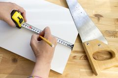 Cropped hands of a carpenter marking white wooden panel with yellow pencil and tape ruler, saw is lying nearby royalty free stock photography