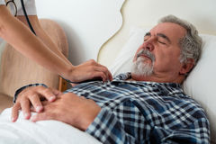 Cropped hands of doctor listening to heartbeats of senior man sleeping on bed Royalty Free Stock Photography