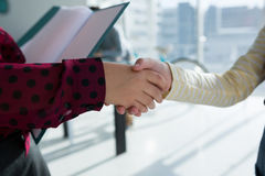 Cropped hands of female colleagues giving handshake. In office Stock Images