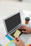 Cropped hands of graphic designer holding adhesive note while using laptop Royalty Free Stock Photo