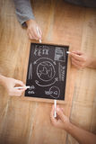 Cropped hands holding chalk with business terms on slate Royalty Free Stock Image