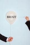 Cropped hands holding needle and popping balloon against light blue background with text saying Brexit Stock Photo