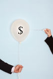 Cropped hands holding needle and popping balloon with Dollar Symbol.  royalty free stock images