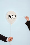 Cropped hands holding needle and popping balloon with text saying POP.  royalty free stock photography