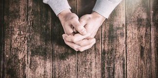Cropped hands of man praying. On wooden desk stock photo