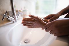 Cropped hands of mother assisting girl while washing hands stock image