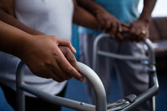 Cropped hands of nurse assisting woman in walking with walker. Cropped hands of nurse assisting women in walking with walker at retirement home Stock Images