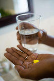 Cropped hands of person holding medicines and drinking water. In bathroom at home Royalty Free Stock Photo