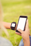 Cropped hands of person wearing smart watch and holding smartphone Stock Images