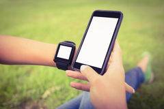 Cropped hands of person wearing smart watch and holding smartphone at park Stock Photo