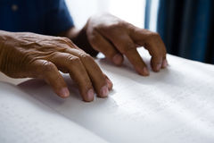 Cropped hands on retired man reading braille book in retirement home. Cropped hands on retired man reading braille book at table in retirement home Stock Image