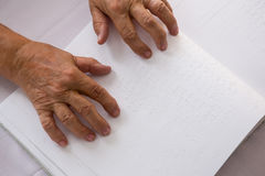 Cropped hands of senior woman reading braille in nursing home. Overhead cropped hands of senior woman reading braille in nursing home Stock Photo