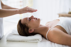 Cropped hands of therapist performing reiki on woman. Cropped hands of therapist performing reiki on young woman at spa Royalty Free Stock Photography