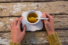 Cropped hands of woman with tea. At wooden table Stock Photography