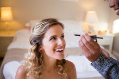 Cropped hands of woman applying makeup to bride in dressing room Stock Photos