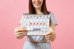 Cropped happy woman in blue dress, hat hold in hand pregnancy test, periods calendar for checking menstruation days. Isolated on pink background. Medical stock images