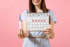 Cropped happy woman in blue dress, hat hold in hand pregnancy test, periods calendar for checking menstruation days. Isolated on pink background. Medical stock photo