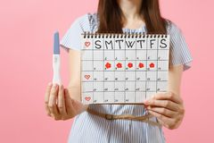 Cropped happy woman in blue dress, hat hold in hand pregnancy test, periods calendar for checking menstruation days. Isolated on pink background. Medical stock image
