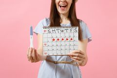 Cropped happy woman in blue dress, hat hold in hand pregnancy test, periods calendar for checking menstruation days. Isolated on pink background. Medical royalty free stock image
