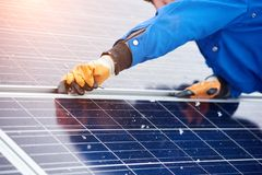 Professional electrician worker installing solar panels. Cropped horizontal shot of a male worker installing solar panels on a power plant using elternative Royalty Free Stock Image