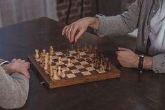 Cropped image of adult son and senior father playing chess together. At home royalty free stock photography