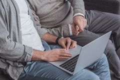Cropped image of adult son and senior father using laptop together. At home royalty free stock photos