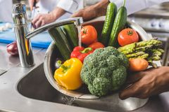 cropped image of african american chef washing vegetables royalty free stock photo