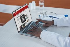Cropped image of african american doctor reading news on a. BBC website Stock Photography