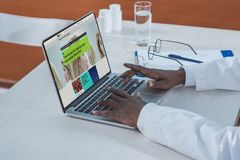 Cropped image of african american doctor reading news. On a laptop Stock Images