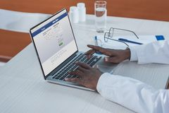 Cropped image of african american doctor sitting with laptop and open. Facebook page Royalty Free Stock Images
