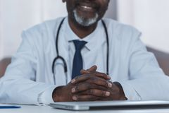 Cropped image of african american doctor sitting at the table. With crossed hands Stock Photography