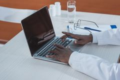 Cropped image of african american doctor typing. On a laptop Stock Photography