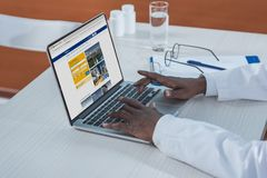 Cropped image of african american doctor using. Booking website Royalty Free Stock Photo