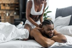 Cropped image of african american girlfriend. Doing massage for boyfriend in bedroom stock image