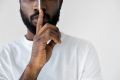 Cropped image of african american man with white stripe on face showing silence sign. Isolated on white stock photo