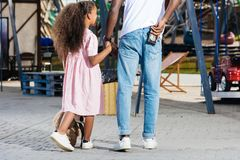 cropped image of african american police officer walking with daughter and holding police badge stock photo