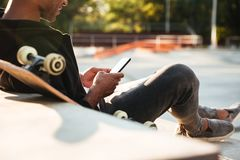 Cropped image of an african guy using mobile phone. While having rest in urban zone Stock Images