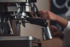 Afro American barista. Cropped image of Afro American barista preparing coffee using a coffee machine, focus on machine details Stock Photography