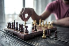 Father and son. Cropped image of Afro American man playing chess, one angle of the chessboard in focus, on wooden table royalty free stock images