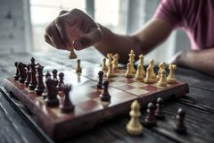 Father and son. Cropped image of Afro American man playing chess, on wooden table stock image