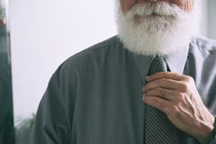 Businessman adjusting tie. Cropped image of aged bearded entrepreneur adjusting necktie royalty free stock photos