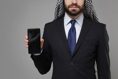Cropped image of arabian muslim businessman in keffiyeh kafiya ring igal agal suit isolated on gray background