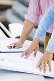 Cropped image of architects with blueprints on car at site Royalty Free Stock Photography